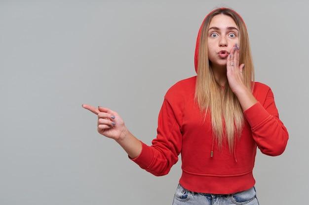 Mulher jovem e bonita loira espantada com sardas em um capuz vermelho mantendo a mão na bochecha e apontando para copyspace na parede cinza