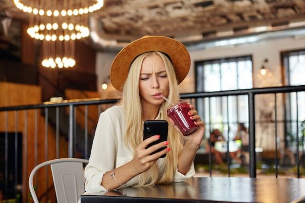 Mulher jovem e bonita loira perplexa com cabelo comprido olhando para a tela de seu telefone e sobrancelhas franzidas, verificando a caixa de correio enquanto espera por seus amigos no café da cidade