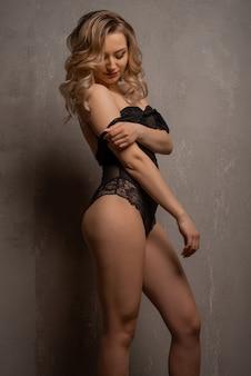 Mulher jovem e bonita loira posando em body de renda preta no estúdio perto da parede.