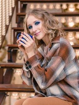 Mulher jovem e bonita loira sentada na escada do carrossel e bebendo café no parque