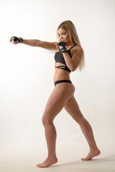 Mulher jovem e bonita loira sexy boxe posando com luvas na parede branca