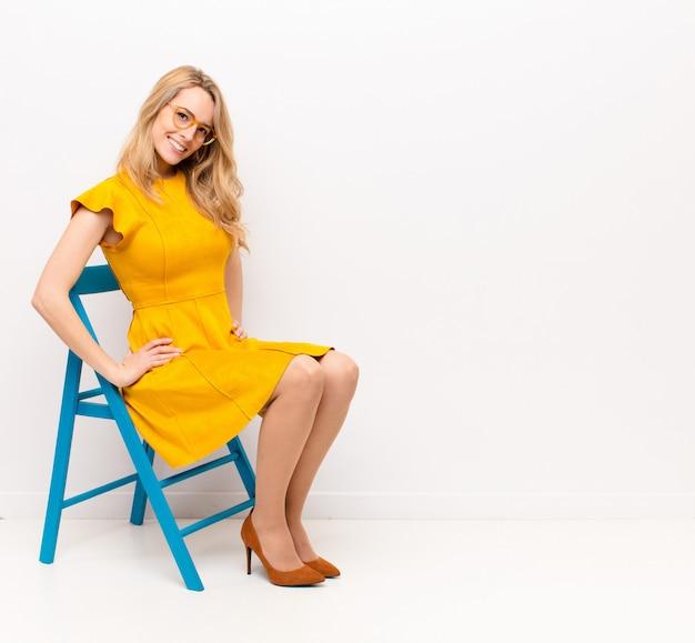 Mulher jovem e bonita loira sorrindo alegre e casualmente com uma expressão positiva, feliz, confiante e relaxada contra uma parede plana de cor