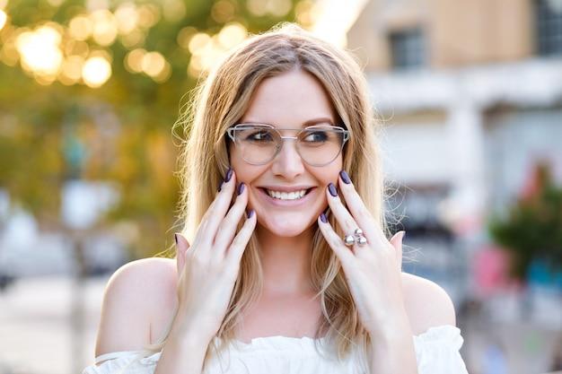 Mulher jovem e bonita loira sorrindo e fazendo careta, óculos transparentes e camisa branca, posando no parque da cidade