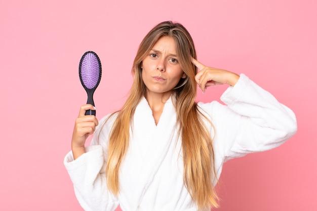 Mulher jovem e bonita loira usando roupão de banho e segurando uma escova de cabelo