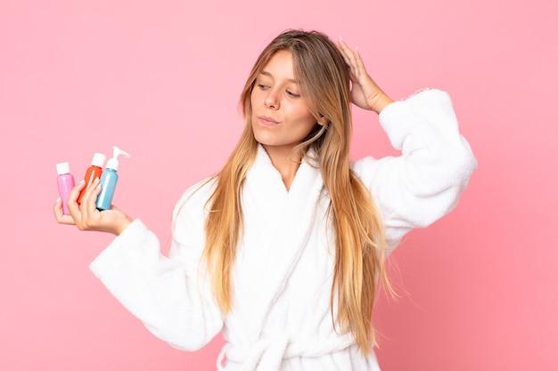 Mulher jovem e bonita loira vestindo roupão de banho e segurando um produto cosmético