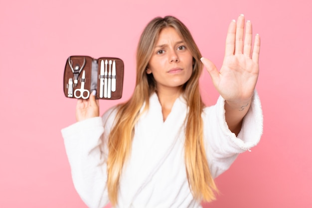 Mulher jovem e bonita loira vestindo roupão de banho e segurando uma bolsa de maquiagem com ferramentas de unhas
