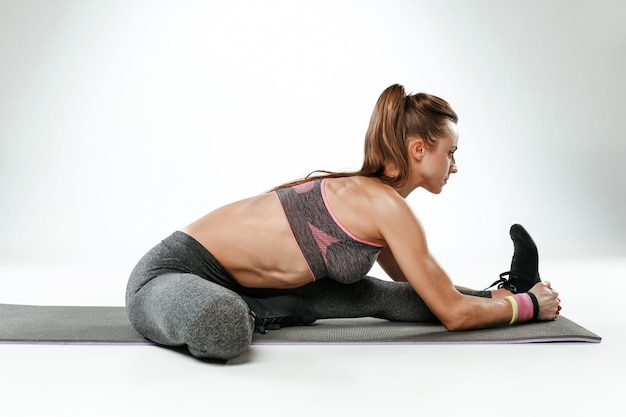 Mulher jovem e bonita magro fazendo exercícios de alongamento na academia contra um fundo branco