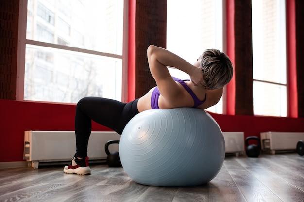 Mulher jovem e bonita magro fazendo ginástica no ginásio com fitball