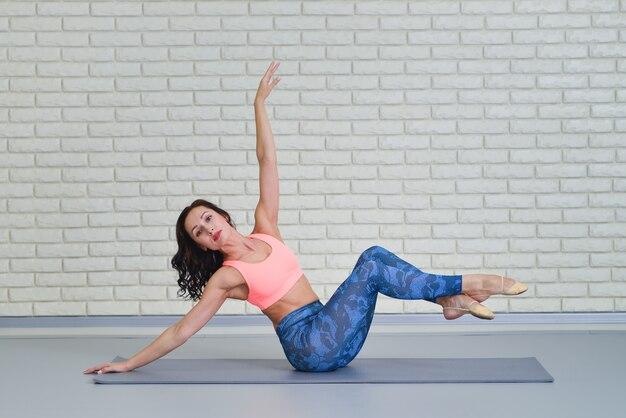 Mulher jovem e bonita malhando na aula de fitness, exercício de equilíbrio