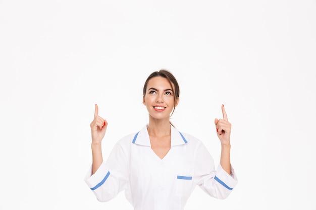 Mulher jovem e bonita médica usando uniforme em pé, isolado na parede branca, apontando para o espaço da cópia