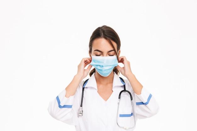Mulher jovem e bonita médica vestindo uniforme em pé, isolado na parede branca, colocando uma máscara