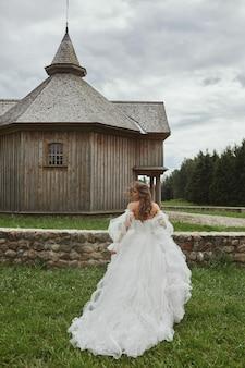 Mulher jovem e bonita modelo em vestido de noiva luxuoso andando no prado no campo ...