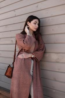 Mulher jovem e bonita moderna com cabelo bonito em um casaco de primavera longa juventude com bolsa de couro na moda relaxa perto de parede vintage de madeira na cidade. menina europeia com roupas elegantes, posando na rua.