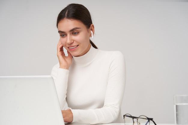 Mulher jovem e bonita morena alegre com penteado de rabo de cavalo, mantendo as mãos no teclado enquanto verifica a caixa de correio em seu laptop, isolado sobre a parede branca