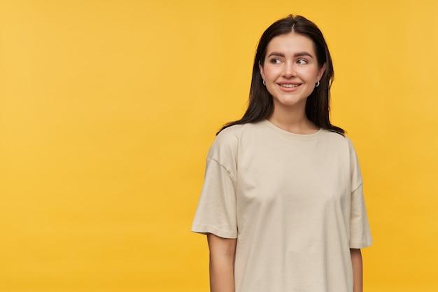 Mulher jovem e bonita morena alegre em uma camiseta branca em pé e olhando para o lado no espaço vazio sobre a parede amarela