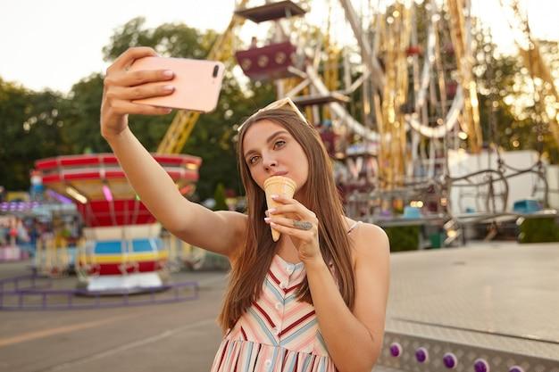 Mulher jovem e bonita morena com cabelo comprido em pé sobre a decoração do parque de diversões, segurando o smartphone na mão e fazendo uma foto de si mesma com casquinha de sorvete