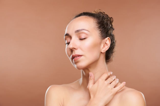 Mulher jovem e bonita morena com os olhos fechados e os ombros nus tocando seu pescoço durante um procedimento de beleza no salão spa
