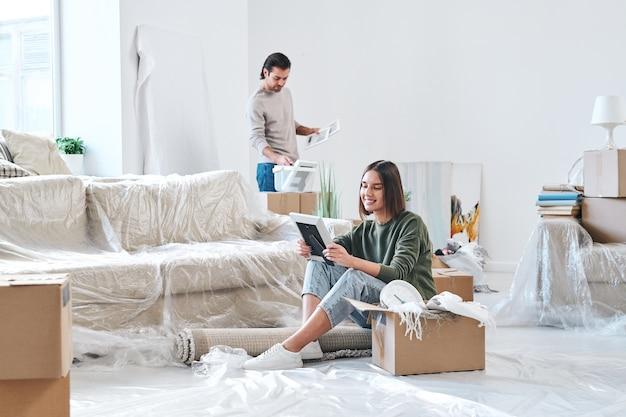 Mulher jovem e bonita morena olhando para a foto em moldura de madeira enquanto está sentada no chão de um apartamento ou casa nova