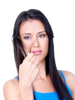 Mulher jovem e bonita morena olhando para as pontas emaranhadas de seus cabelos longos - isolado