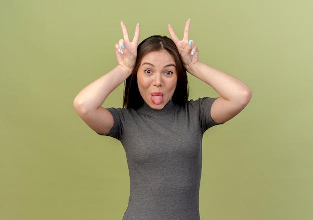 Mulher jovem e bonita mostrando a língua e fazendo orelhas de coelho isoladas em um fundo verde oliva com espaço de cópia