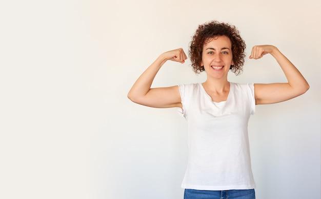 Mulher jovem e bonita mostrando bíceps expressando força e boa saúde