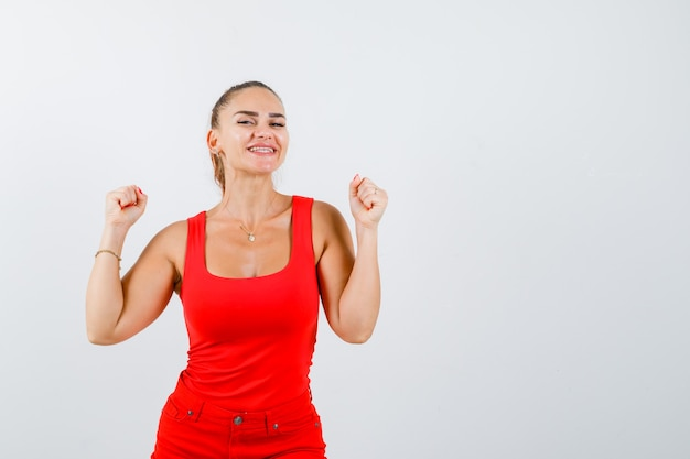 Mulher jovem e bonita mostrando o gesto do vencedor em um top vermelho e olhando feliz, vista frontal.
