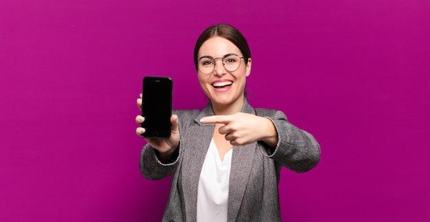 Mulher jovem e bonita mostrando seu telefone de tela vazia. conceito de negócios
