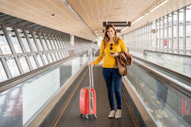 Mulher jovem e bonita muito feliz andando na esteira no aeroporto com sua bagagem