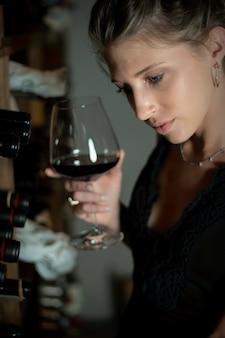 Mulher jovem e bonita na adega com vinhos