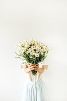 Mulher jovem e bonita na blusa bege segura nas mãos um buquê de flores de margarida de camomila branca em branco.