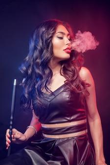 Mulher jovem e bonita na boate ou bar fuma um cachimbo de água ou shisha
