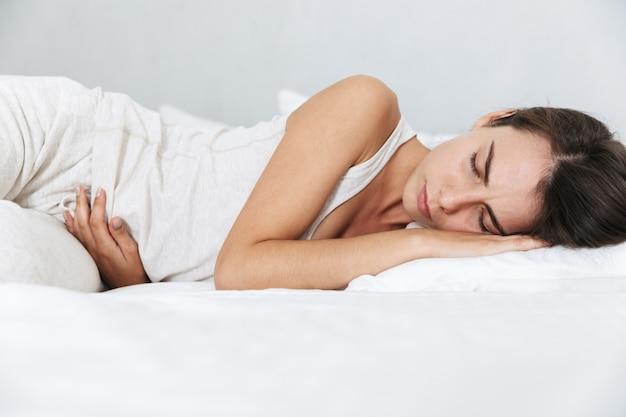 Mulher jovem e bonita na cama em casa, com dor de estômago