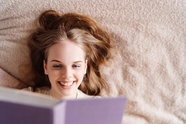 Mulher jovem e bonita na cama em casa curtindo o livro favorito
