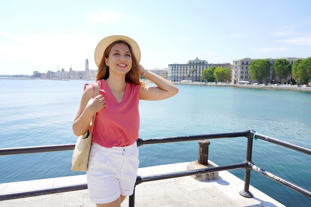 Mulher jovem e bonita na costa do mar contra a paisagem urbana de bari, apúlia, itália