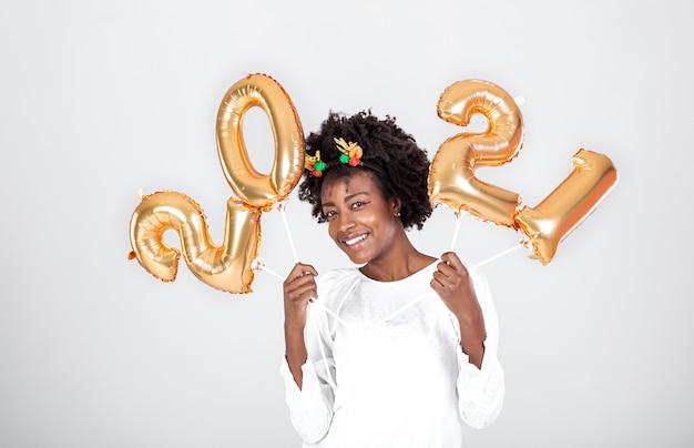 Mulher jovem e bonita na festa de ano novo sobre fundo branco do estúdio com balões de ouro