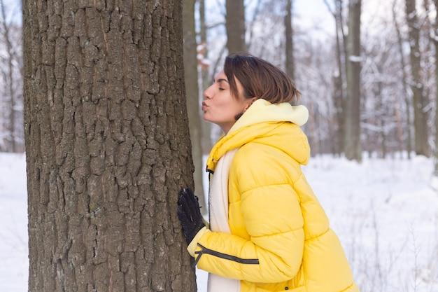 Mulher jovem e bonita na floresta de inverno mostra ternos sentimentos pela natureza, mostra seu amor pela árvore