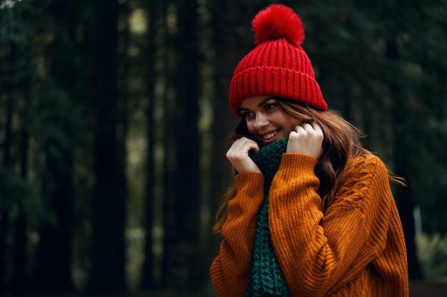 Mulher jovem e bonita na floresta em roupas brilhantes, um chapéu vermelho, um suéter laranja, com um lenço verde viaja, caminhadas na natureza na floresta