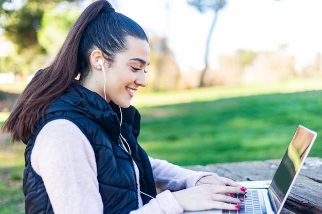 Mulher jovem e bonita na linha de navegação nas mídias sociais com um laptop