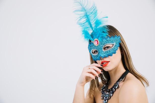 Mulher jovem e bonita na máscara de carnaval posando em pano de fundo branco