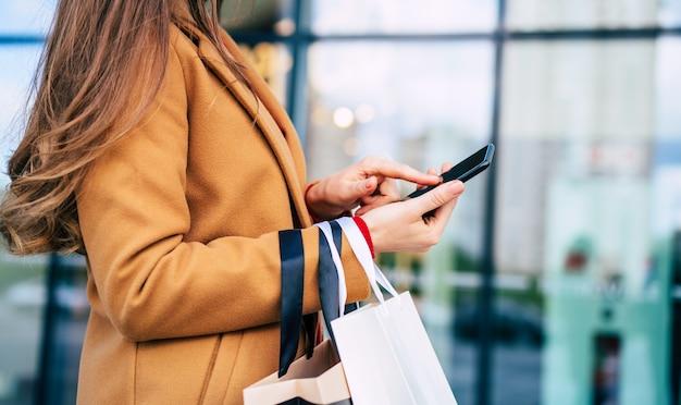 Mulher jovem e bonita na moda com muitas sacolas coloridas de bom humor com telefone inteligente e cartão de crédito enquanto caminhava no shopping durante a sexta-feira negra