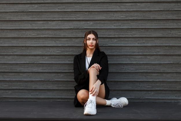 Mulher jovem e bonita na moda com roupas elegantes de juventude, sentada perto de uma parede vintage