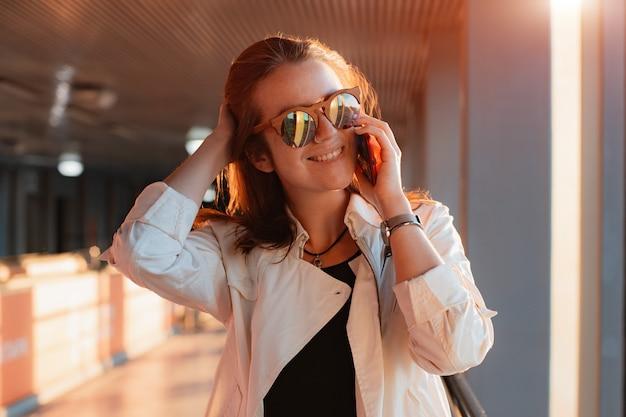 Mulher jovem e bonita na moda em óculos de sol com um smartphone celular nas mãos dela se comunica ao telefone no meio urbano urbano do túnel nos raios do sol. Foto Premium