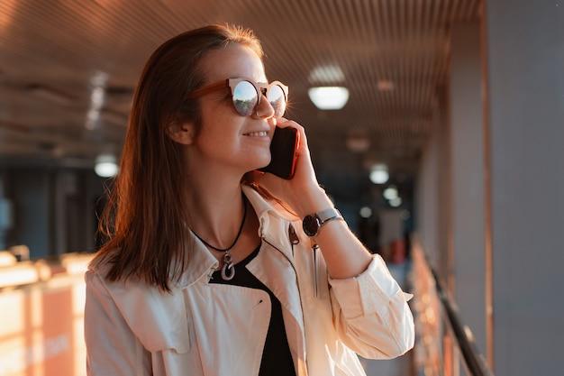 Mulher jovem e bonita na moda em óculos de sol com um smartphone celular nas mãos dela se comunica ao telefone no meio urbano urbano do túnel nos raios do sol.