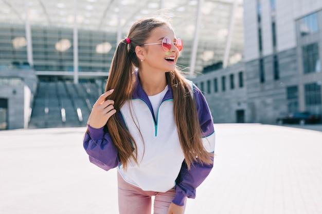 Mulher jovem e bonita na moda em roupas elegantes, usando óculos de sol rosa e rindo