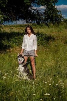 Mulher jovem e bonita na moda em shorts jeans e uma blusa branca posando no parque com um husky