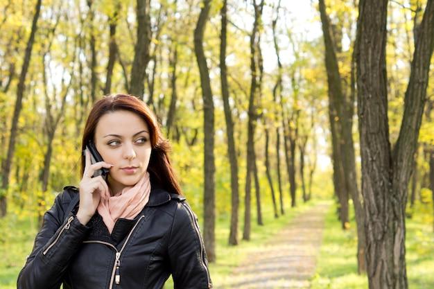 Mulher jovem e bonita na moda esperando uma ligação em seu telefone celular enquanto está em um caminho