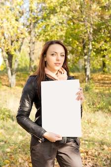 Mulher jovem e bonita na moda segurando um cartaz em branco para o seu texto nas mãos, ao ar livre
