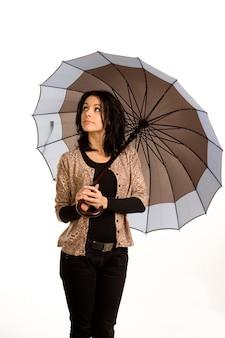 Mulher jovem e bonita na moda segurando um guarda-chuva enquanto olha para o céu para verificar o tempo