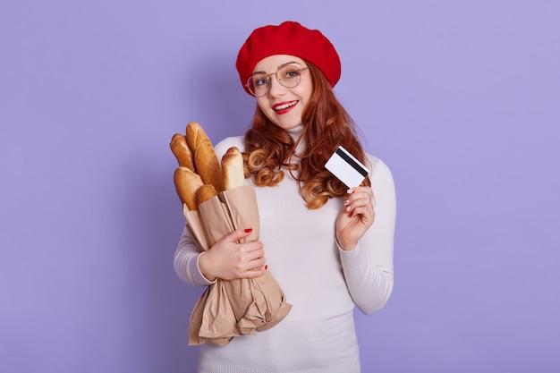 Mulher jovem e bonita na padaria comprando pacote com baguetes