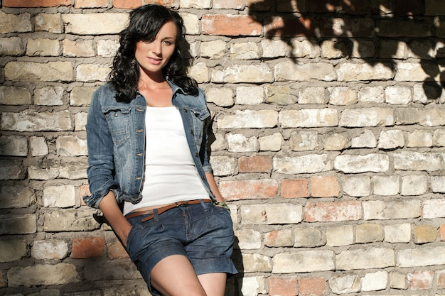 Mulher jovem e bonita na parede de tijolo